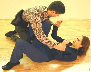 Wing Tsun Exercise 100, Fig. 1 - The opponent hold her by the wrists.  Her Tan-Gerk-barrier helps to hold him back.