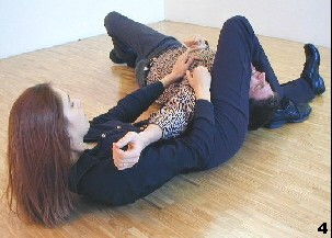 Wing Tsun Exercise102, Fig 4 - She applies a scissors strech to the opponents neck