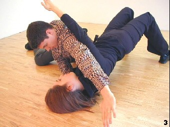 Wing Tsun Exercise 107 , Fig 3 - She manages to palce her arm underneath his armpit and lifts up her hip quickly