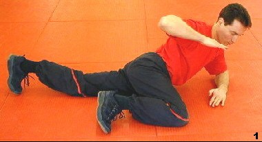 Wing Tsun Course, Fig. 2 - Sifu is lying on the foor bending his right leg